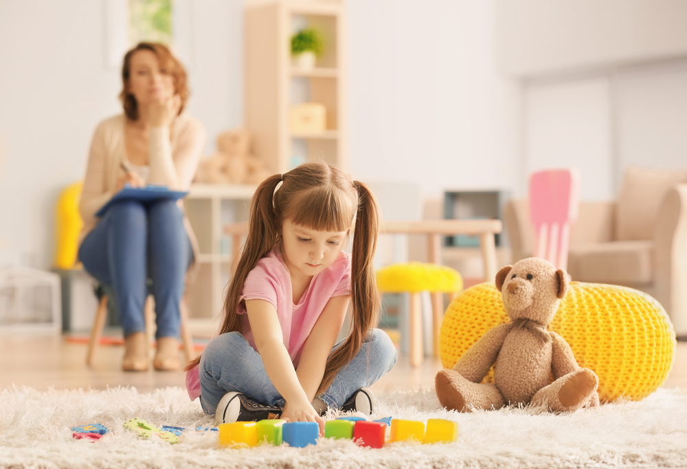 Cute little girl during play therapy at psychologist's office