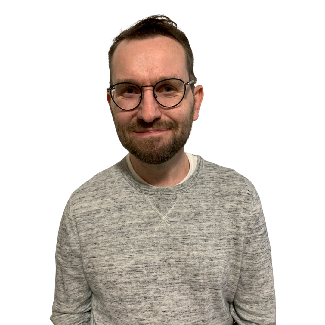 Justin Doyle, man wearing grey sweater with glasses